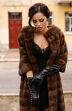 Gorgeous sensual woman with dark hair in luxurious fur coat and leather gloves royalty free stock photography