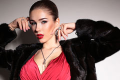 Gorgeous sensual woman with elegant hairstyle,wears red dress and fur coat Royalty Free Stock Images