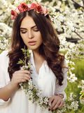 Gorgeous sensual woman with luxurious hair in elegant dress posing in blossom garden Stock Photo