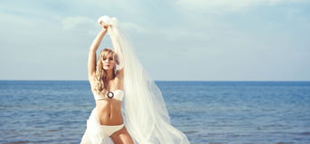 Gorgeous, sexy blond posing with blowing silk on the beach. Royalty Free Stock Images