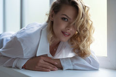 Gorgeous sexy blonde lying on window sill portrait. Gorgeous curly blonde in white shirt lying on window sill portrait Stock Photo