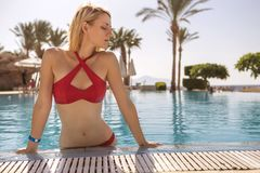 Gorgeous blonde slim woman with fit body in red swimsuit sw. Imming on a pool on a vacation in tropical resort. Outdoor. Summer sunny day. Relax in water. Copy royalty free stock image