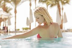 Gorgeous blonde slim woman with fit body in red swimsuit sw. Imming on a pool on a vacation in tropical resort. Outdoor. Summer sunny day. Relax in water. Copy royalty free stock photography
