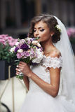 Gorgeous sexy bride in vintage dress smelling bouquet of flowers Stock Images