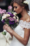 Gorgeous sexy bride in vintage dress smelling bouquet of flowers Royalty Free Stock Images