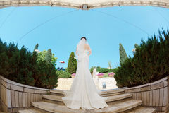Gorgeous sexy bride in white dress posing on street. Back of bride with bridal bouquet standing on stairs in park ander modern roof. Fisheye lens photo Stock Photo