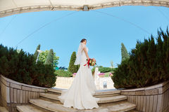 Gorgeous sexy bride in white dress posing on street. Bride with bridal bouquet standing on stairs outdoors. Fisheye lens photo Stock Photos