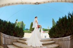 Gorgeous sexy bride in white dress posing on street Stock Photos