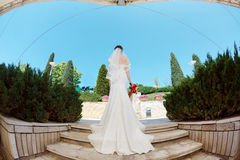 Gorgeous sexy bride in white dress posing on street. Full body of bride with bridal bouquet standing on stairs in park ander modern roof. Fisheye lens photo Stock Photography