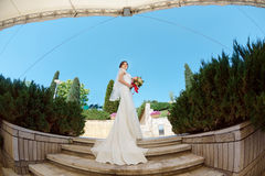 Gorgeous sexy bride in white dress posing on street. Young sexy bride with bridal bouquet posing outdoors in park. Fisheye lens photo Royalty Free Stock Photo