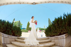 Gorgeous sexy bride in white dress posing on street. Young happy bride with bridal bouquet posing outdoors in park. Fisheye lens photo Stock Photo