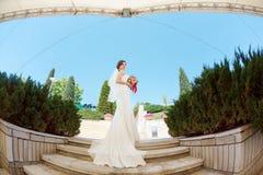 Gorgeous sexy bride in white dress posing on street Stock Photo