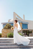 Gorgeous sexy bride in white dress posing on street. Young happy bride with bridal bouquet posing outside against modern building Stock Photography