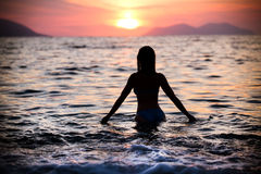 Gorgeous sexy fit woman silhouette swimming in sunset.Free happy woman enjoying sunset. Beautiful woman in water embracing the gol Royalty Free Stock Photography
