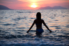 Gorgeous fit woman silhouette swimming in sunset.Free happy woman enjoying sunset. Beautiful woman in water embracing the gol Stock Photo