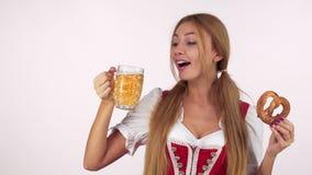 Gorgeous German waitress in dirndl drinking beer, holding delicious pretzel stock photos