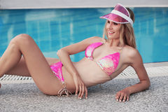 Gorgeous sexy girl with blond hair in elegant bikini relaxing beside swimming pool Stock Images