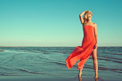 Gorgeous sexy slim blond model in red strapless dress with flying train standing on tiptoe in the sea water. Holding her wavy hair blown by the wind. Copy Royalty Free Stock Image