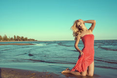 Gorgeous sexy slim blond model in red strapless dress standing on knees in the sea water. With closed eyes, one hand on her head, another one holding the train Royalty Free Stock Image