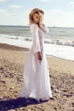Gorgeous woman with blond curly hair in elegant beach dress Royalty Free Stock Image