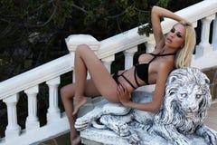 Gorgeous sexy woman with blond hair in elegant bikini. Fashion outdoor photo of gorgeous sexy woman with blond hair in elegant bikini posing on park Stock Photo