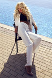 Gorgeous sexy woman with blond hair in luxurious white suit Stock Photo