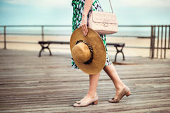 Gorgeous woman wearing summer dress, shoes, pink bag, holding hat and walking on seashore boardwalk at sunset time. Stock Photo