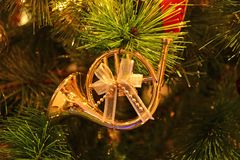 Gorgeous Shiny Gold French Horn Shaped with Ribbon Bow Christmas Ornament Hanging on Sparkling Christmas Tree. Happy holiday stock photo