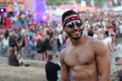 Gorgeous shirtless man standing out for the crowd.  royalty free stock photography
