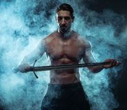 Gorgeous Shirtless Muscled Man Holding a Sword Stock Photo