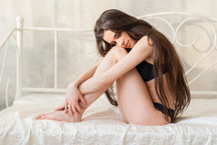 Gorgeous slender girl in lingerie sitting on the bed Royalty Free Stock Photos