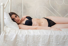 Gorgeous slim girl in lingerie lying on a bed Stock Photography