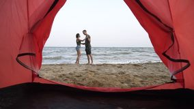 Gorgeous slow motion footage of young couple embaracing, standing in front the sea. Romantic, feelings. Footage from. Inside of a camp tent stock video footage