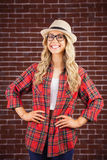 Gorgeous smiling blonde hipster with hands on hips Stock Image