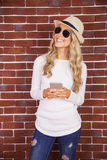 Gorgeous smiling blonde hipster holding smartphone Stock Photos