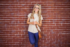 Gorgeous smiling blonde hipster leaning against red brick background Royalty Free Stock Photos