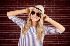 Gorgeous smiling blonde hipster posing with straw hat Royalty Free Stock Image