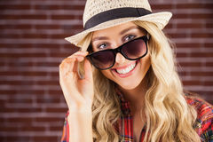 Gorgeous smiling blonde hipster posing with sunglasses Royalty Free Stock Image
