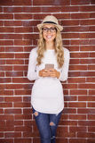 Gorgeous smiling blonde hipster with smartphone Royalty Free Stock Image