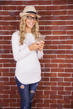 Gorgeous smiling blonde hipster using smartphone Royalty Free Stock Photos