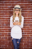 Gorgeous smiling blonde hipster using smartphone Stock Photo