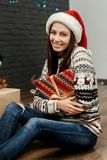 Gorgeous smiling brunette girl in santa hat and cozy sweater hol Royalty Free Stock Images