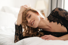 Gorgeous smiling brunette woman lies on bed Stock Images