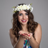 Gorgeous smiling fairy beauty with flowers tiara giving something Royalty Free Stock Photography