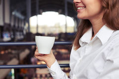 Gorgeous smiling female in white shirt enjoying cup of espresso Stock Photography