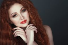 Gorgeous smiling red headed woman with beautiful make up, her hands crossed under her chin. Close up portrait of a gorgeous smiling red headed woman with Royalty Free Stock Images