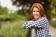 Gorgeous smiling redhead leaning against bridge Royalty Free Stock Image