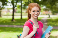 Gorgeous smiling student holding notebooks looking at camera Royalty Free Stock Images
