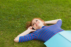 Gorgeous smiling student lying on grass phoning. On campus at college Stock Photography