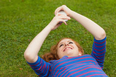 Gorgeous smiling student lying on grass texting. On campus at college Stock Photos